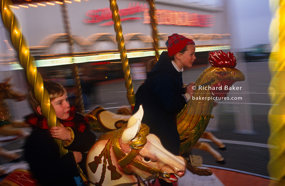 Two children ride a merry-go-round on the sea front at Southport, Merseyside, northern England. Hanging on to the carousel's horse, the youngest child is a boy who grips the pole as he whizzes through along while an older girl who is possibly his sister, leans forward as she enjoys the circular speed. The background blurs but we see the bright lights above the pier's amusement arcade entrance (the second longest pier in the UK) but it is a chilly winter, an off-season day with few people about on this chilly day nearing Christmas.