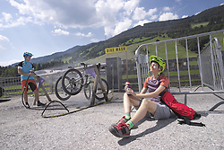 Mountain bikers relaxing after bike tour and her friend cleaning bicycles, Zillertal, Tyrol, Austria