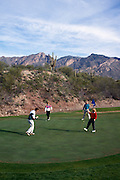 Foursome putting on green, Canyon hole #4. Santa Catalina Mountains behind. ©1993 Edward McCain. All rights reserved. McCain Photography, McCain Creative.