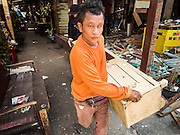 21 SEPTEMBER 2015 - BANGKOK, THAILAND: A demolition worker pulls an upright cabinet out of a home being razed near Wat Kalayanamit. Fiftyfour homes around Wat Kalayanamit, a historic Buddhist temple on the Chao Phraya River in the Thonburi section of Bangkok are being razed and the residents evicted to make way for new development at the temple. The abbot of the temple said he was evicting the residents, who have lived on the temple grounds for generations, because their homes are unsafe and because he wants to improve the temple grounds. The evictions are a part of a Bangkok trend, especially along the Chao Phraya River and BTS light rail lines. Low income people are being evicted from their long time homes to make way for urban renewal.    PHOTO BY JACK KURTZ