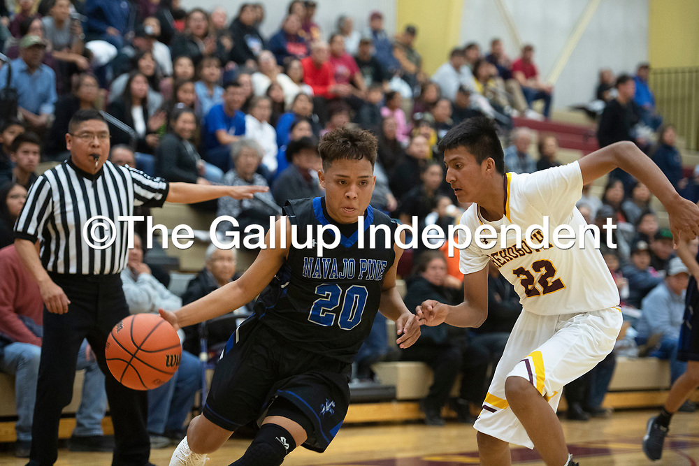 Navajo Pine Warrior Dempsey Lincoln (20) drives to the basket as Rehoboth Lynx Mato Chapman (22) defends Tuesday evening in Rehoboth.