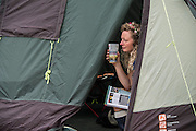 Looking out at the gloom and reading the festival guide from the santuary of her tent - The 2016 Glastonbury Festival, Worthy Farm, Glastonbury.
