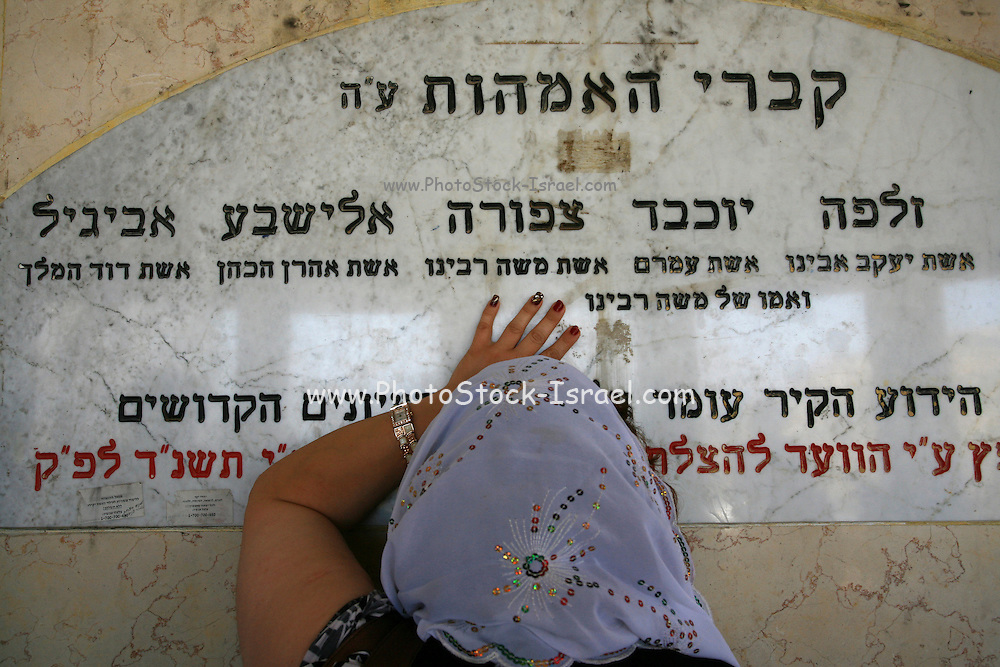 "Israel, Galilee, Tiberias, Woman prays at the tomb of ""the holy mothers"" holy place in Tiberias. People come from all over to pray at this site as they attribute special abilities to this holy place"