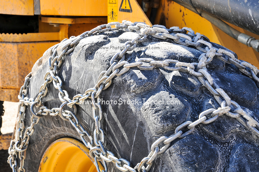 Heavy Earth moving equipment with snow chains on its tyres