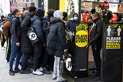 © Licensed to London News Pictures. 02/12/2020. London, UK. A security guard speaks to shoppers at a branch of JD sports on Oxford Street. Today England returns to tiered COVID restrictions following the end of the second national lockdown. Photo credit: George Cracknell Wright/LNP