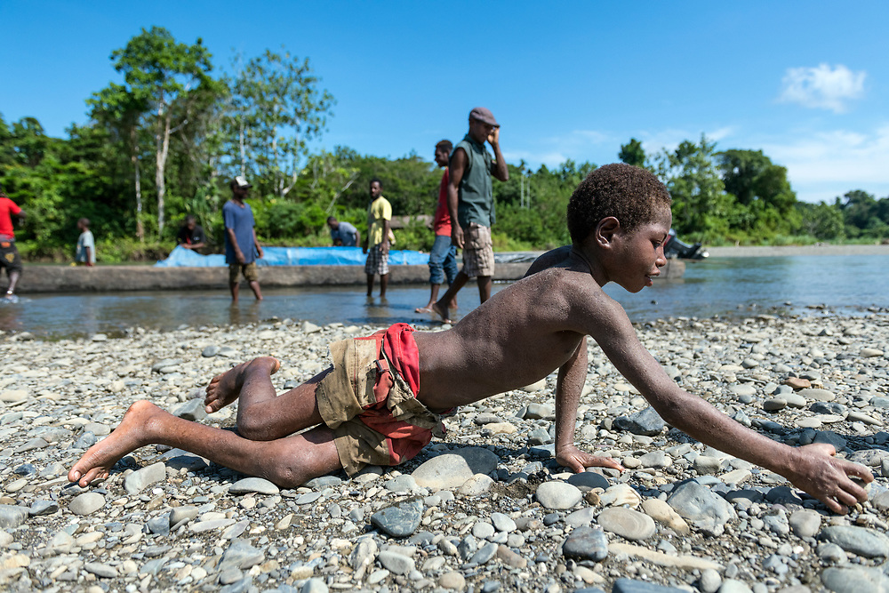 A boy reaches for a stone on the Clay River in the village of Likan, East Sepik Province, Papua New Guinea.