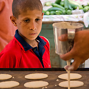 With his eye on the prize, a young boy imagines how good these cookies at Rashid market would taste.