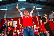 27 JULY 2013 - BANGKOK, THAILAND:   A Thai Red Shirt entertainer leads Red Shirts in wishing Thaksin Shinawatra a happy birthday during the party for Thaksin Shinawatra. The Red Shirts celebrated former Prime Minister Thaksin Shinawatra's 64th birthday with a party at Phibun Prachasan School in Bangkok. They had a Buddhist Merit Making Ceremony, dinner, cake and entertainment. Most of the Red Shirt political elite traveled to Hong Kong for a party with Thaksin. Thaksin, the former Prime Minister, was deposed by a coup in 2006 and subsequently convicted of corruption related crimes. He went into exile rather than go to jail but remains very popular in rural parts of Thailand. His sister, Yingluck Shinawatra is the current Prime Minister and was elected based on her brother's recommendation.   PHOTO BY JACK KURTZ
