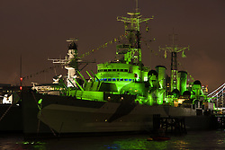 © Licensed to London News Pictures. 17/03/2013. London, UK. HMS Belfast is lit up in green at night on the River Thames in London on 17 March 2013. This marks the 75th anniversary of HMS Belfast which also falls on St Patrick's Day. Photo credit : Vickie Flores/LNP
