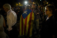 A man wrapped in a Cataln flag gets interviwed during the rally
