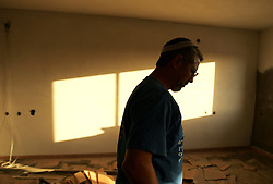 A man is seen inside a house under construction, which continues at the Newe Deqalim settlement, despite Israel's parliament recently supporting compensation payments for Jewish settlers leaving the area in Gaza, Palestinian Territories, Nov. 6, 2004. The vote was vital for Prime Minister Ariel Sharon's plan to evacuate the occupied territory.