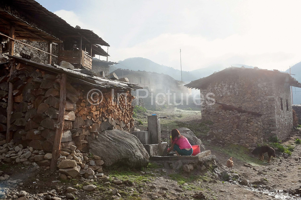 A Brokpa woman washes clothes at the standpipe in the early morning in the remote and roadless village of Merak, Eastern Bhutan. The Brokpa, the semi-nomads of the villages of Merak and Sakteng are said to have migrated to Bhutan a few centuries ago from the Tshona region of Southern Tibet. Thriving on rearing yaks and sheep, the Brokpas have maintained many of their unique traditions and customs. In summer they move to the pastures with their yaks and sheep and in winter they return to live in their houses, normally built of stones with small ventilation to protect from the piercing cold weather.