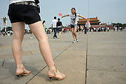 Visitors pose for photos on Tiananmen Square in Beijing, China June 4, 2007. Monday marks the 18th anniversary of the bloody crackdown on pro-democracy demonstrators in which People's Liberation Army troops and tanks crushed the student-led demonstrations in the historic Beijing square on June 4, 1989, killing scores.