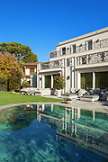 Architecture; beautiful house with pool, blue sky and lush garden