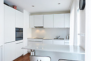 Modern white kitchen with peninsula with design stools. Nobody inside
