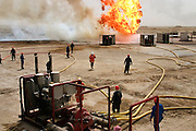 """Firefighters from the Kuwait Oil Company (called KWWK: Kuwait Wild Well Killers) connect hoses to water tanks and a replacement pumps near the second oil well fire they were working on in Iraq's Rumaila Oil field. Later in the day they failed to extinguished this fire with water and then tried to stop the flow of gas and oil with drilling mud using what is called a """"stinger,"""" a tapered pipe on the end of a long steel boom controlled by a bulldozer. Drilling mud, under high pressure, is pumped through the stinger into the well, stopping the flow of oil and gas. This was also unsuccessful. The Rumaila field is one of Iraq's biggest oil fields with five billion barrels in reserve. Many of the wells are 10,000 feet deep and produce huge volumes of oil and gas under tremendous pressure, which makes capping them very difficult and dangerous. Rumaila is also spelled Rumeilah."""