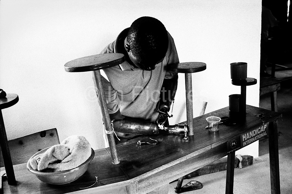 A man works at using his new artificial arm, Handicap International rehab centre, Murraytown Amputee Camp, Freetown, Sierra Leone 1999