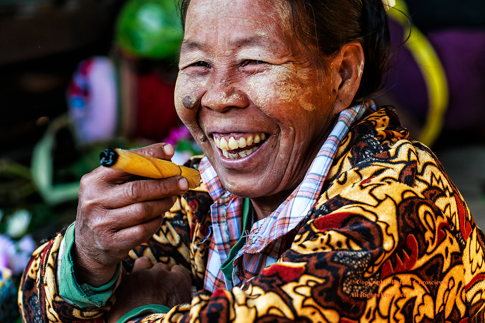 Morning Smoke: A lady laughs with a friend as she smokes from one of the largest hand rolled cigarettes I have ever seen, in the morning market, Shwebo Myanmar.