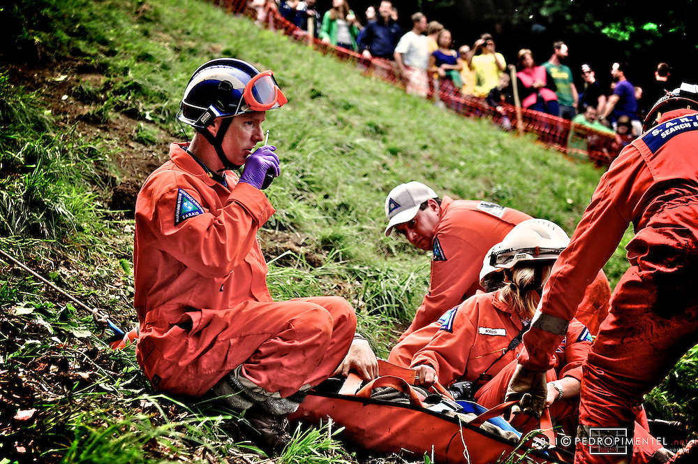 Due to the steepness and uneven surface of the hill there are usually a number of injuries, ranging from sprained ankles to broken bones and concussion. A first aid service is provided by the local St John Ambulance (Gloucester, Cheltenham and Stroud Divisions) at the bottom of the hill, with a volunteer rescue group on hand to carry down to them any casualties who do not end up at the bottom through gravity..Gloucestershire Cheese Rolling festival. Cooper's Hill, UK.