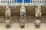 Ancient stone mythical lions and gargoyles on Palazzo Nicolaci di Valladorata in Baroque Noto city, Sicily