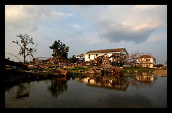 1 June, 2006. Lower 9th Ward, New Orleans, Louisiana. The sun sets on the first day of hurricane season. Reflected misery. Water builds up amidst piles of wreckage in the devastated Lower 9th Ward. With water mains switched back on, ruptured infrastructure permits water to seep to the surface, forming stagnant fetid pools where mosquitos breed unchecked.