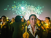 Fireworks go off while Thais hold candles to honor the King. Thais observed the 86th birthday of Bhumibol Adulyadej, the King of Thailand, their revered King on Thursday. They held candlelight services throughout the country. The political protests that have gripped Bangkok were on hold for the day, although protestors did hold their own observances of the holiday. Thousands of people attended the government celebration of the day on Sanam Luang, the large public space next to the Grand Palace in Bangkok.