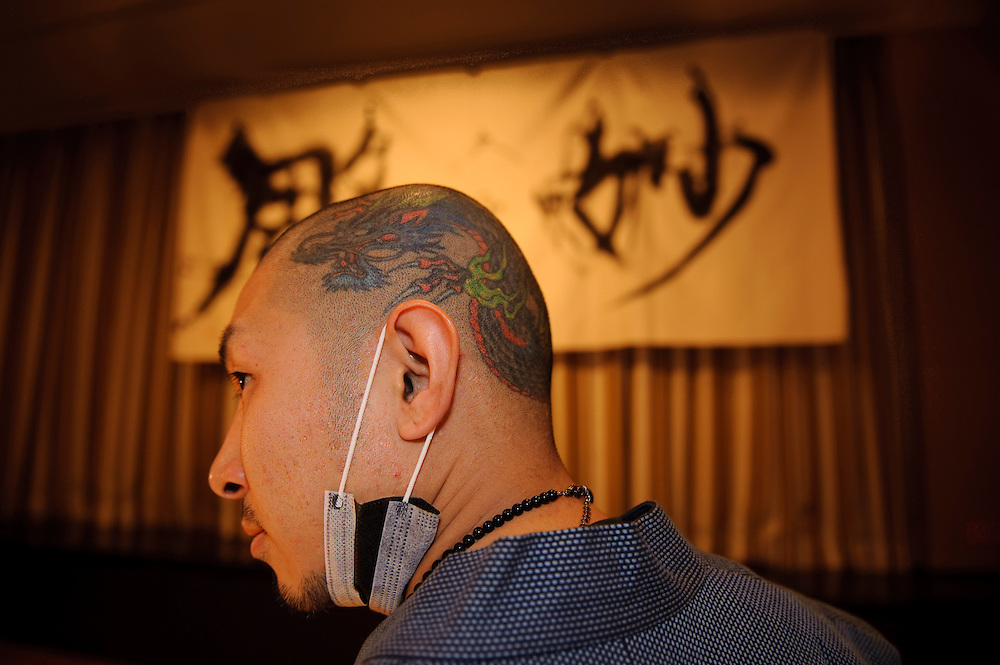 """Tattooist Horimyo in front of a banner bearing his name. Tattoo demonstration, FCCJ, 25 Feb 2009. Author Manami Okazaki and photographer Martin Hladik introduce their book: """"Tattoo in Japan"""" while tattoo master Horimyo gives a demonstration of his art."""