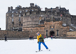 Edinburgh, Scotland, United Kingdom, 1 March, 2018. Heavy snowfalls continue across the city from the storm known as The Beast from the East. Most shops are closed and transport services have been cancelled. Man skiing in front of Edinburgh Castle .