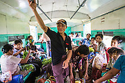 15 JUNE 2013 - YANGON, MYANMAR:  A passenger holds onto the hand rail on the Yangon Circular Train. The Yangon Circular Railway is the local commuter rail network that serves the Yangon metropolitan area. Operated by Myanmar Railways, the 45.9-kilometre (28.5mi) 39-station loop system connects satellite towns and suburban areas to the city. The railway has about 200 coaches, runs 20 times and sells 100,000 to 150,000 tickets daily. The loop, which takes about three hours to complete, is a popular for tourists to see a cross section of life in Yangon. The trains from 3:45 am to 10:15 pm daily. The cost of a ticket for a distance of 15 miles is ten kyats (~nine US cents), and that for over 15 miles is twenty kyats (~18 US cents). Foreigners pay 1 USD (Kyat not accepted), regardless of the length of the journey.     PHOTO BY JACK KURTZ
