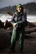 Liana Welty smiles while standing, in rain gear after a rainstorm, at Third Beach, Olympic National Park, Washington.