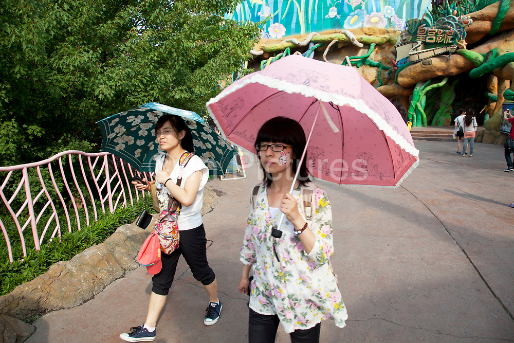 Girls using umbrellas to protect them from the sun. Happy Valley Beijing is an amusement park in Beijing, China built and operated by Beijing OTC, which is part of the Shenzhen OCT Holding Group. The park, which is located in the east of Beijing, opened in July, 2006. It is one of four theme parks in the brand chain. Similar in style with the Disney land park, Happy Valley Beijing also featured distinctive landscapes and themes throughout the resort along with featured rides within the different themes. In total there are more than 40 rides.