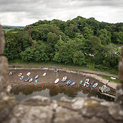 Boats moored on the muddy banks of the River Seiont as seen from the ramparts at Caernarfon Castle in northwest Wales. A castle originally stood on the site dating back to the late 11th century, but in the late 13th century King Edward I commissioned a new structure that stands to this day. It has distinctive towers and is one of the best preserved of the series of castles Edward I commissioned.