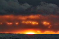 Angry electric clouds at sunrise over the Pacific Ocean from the deck of the MV World Odyssey.  Nikon 1 V3 camera and 70-300 mm lens (ISO 200, 224 mm, f/11, 1/60 sec).