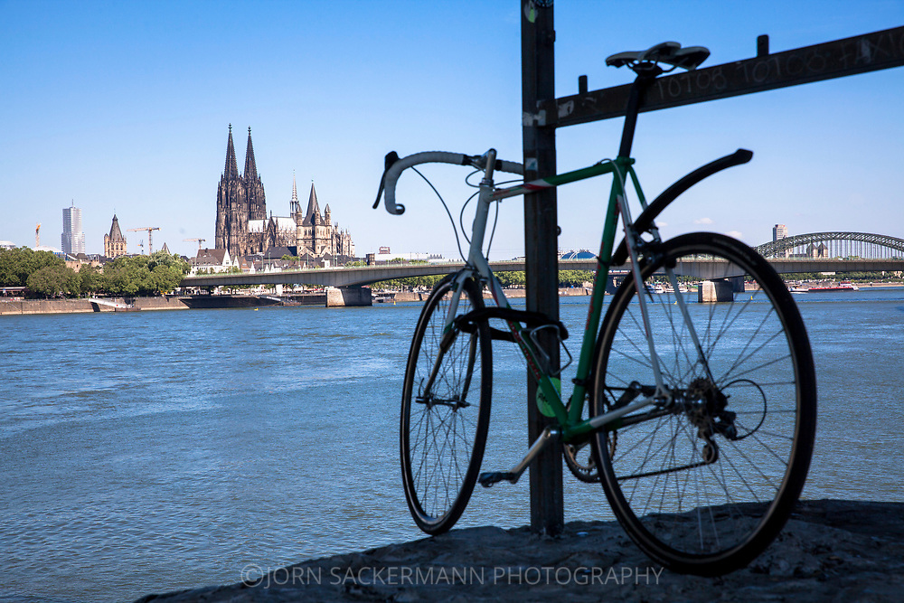 bicycle on the banks of the river Rhine in the district Deutz, view to the city centre with the cathedral, Cologne, Germany.<br /> <br /> Fahrrad am Rheinufer in Deutz, Blick zur Innenstadt mit Dom, Koeln, Deutschland.