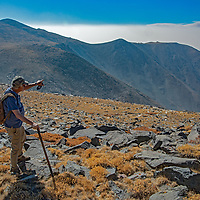 Archaeologist Robert Bettinger stands  at 12,400' in California's White Mountains, the highest Native American settlement in the United States.  Behind is the spectacular Owens Valley and eastern escarpment of the Sierra Nevada, hidden by wildfire smoke.