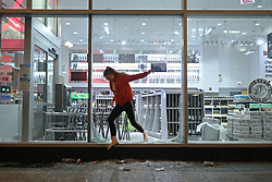 A woman jumps out of a Walgreens store empty-handed after seeing police officers nearby, after a march and rally to remember the May 25 killing of George Floyd by a Minneapolis police officer, in the Loop Saturday, May 30, 2020, in Chicago, IL, USA. Photo by John J. Kim/Chicago Tribune/TNS/ABACAPRESS.COM