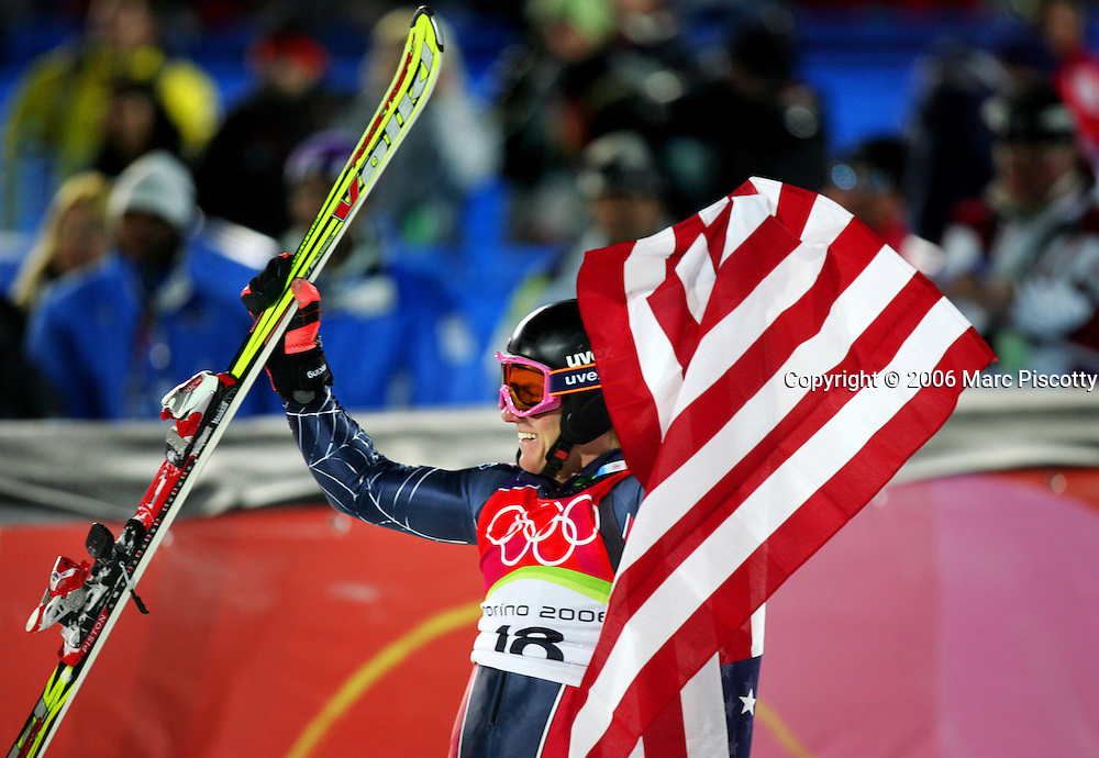 U.S. skiier Ted Ligety celebrates with the U.S. flag after realizing he's won the gold medal in the Men's Combined at Sestriere Colle Tuesday February 14, 2006. He had to wait out the runs of eventual silver medalist Ivica Kostelic of Croatia and Benjamin Raich of Austria who didn't finish the second run. American skiier Ted Ligety won the gold medal with combined downhill and slalon times of 3:09.35. Teammate Bode Miller had led all skiiers after the downhill but was disqualified on his first slalom run after stradling a gate..(Photo by Marc Piscotty / © 2006)