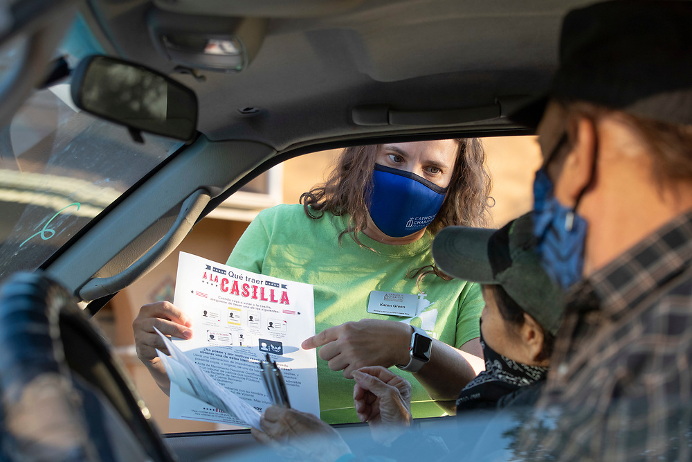 Catholic Charities workers including Karen Green help Texas residents check voter registration status and help fill out voter applications during a four-hour drive-thru on October 1, 2020 in Austin.  Several dozen mostly Hispanic U.S. residents were signed up in the non-partisan effort.