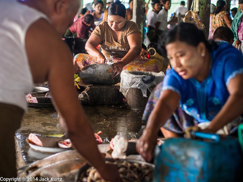 08 NOVEMBER 2014 - SITTWE, RAKHINE, MYANMAR:  A woman butchers a fish in the market in Sittwe. Sittwe is a small town in the Myanmar state of Rakhine, on the Bay of Bengal.  PHOTO BY JACK KURTZ