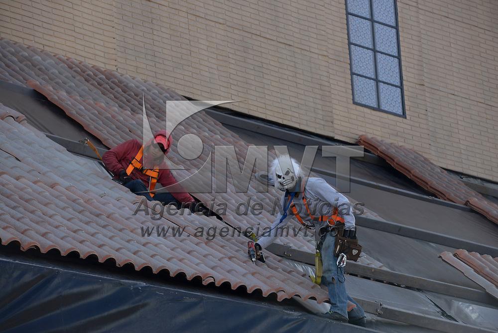 Toluca, México (Octubre 27, 2016).- Un hombre que trabaja en la instalación de la replica de la Capilla Sixtina en la Plaza de los Mártires, trabajo con una mascara de calavera, por la próxima celebración del Día de Muertos, poniendo un poco de color a su trabajo.  Agencia MVT / Crisanta Espinosa