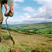 Using a peat cutter, gamekeeper Don Herd turfs the shooting butts where the 'guns' stand on a grouse shooting day, Upper Nidderdale, North Yorkshire, UK