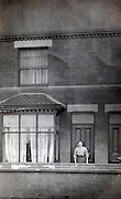 woman standing infront of the door of her house 1900s England