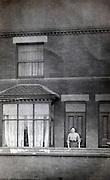 woman standing infront of the door of her house 1900s England
