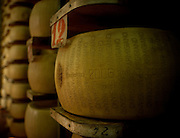 A closeup of a wedge of cheese sitting on a shelf with hundreds of other in the factory in Parma, Italy