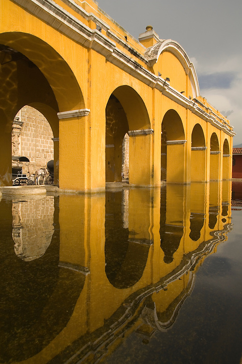 Central America, Guatemala, Sacatepéquez department, Antigua, yellow collonade of arches and reflection.