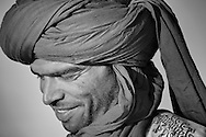 Portrait of a smiling Moroccan man wearing a traditional turban.  Black and white fine art image.