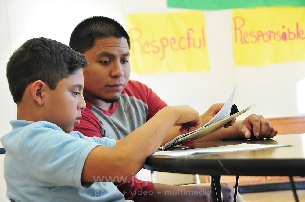 Hartnell College sophomore Stephen Corona, 24, helps Yacer Picazo, a Sherwood Elementary School student, with his English reading. Tutoring for area children in many subjects is also available at the nearby Los Padres Learning Center and the Cesar Chavez Library.