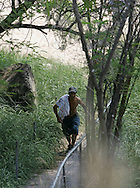Photo by Alex Jones..An illegal immigrant walks up stairs from the Rio Grande toward the Roma Bluffs after crossing the Rio Grande in Roma, Texas on June 14.  After seeing a photographer ahead, the immigrant turned around and disappeared into the brush.
