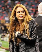 Actor and singer Miley Cyrus hangs out on the Saints sidelines and poses with Saints owner Rita Benson Leblanc prior to the kick off against the St. Louis Rams.The New Orleans Saints play the St. Louis Rams in New Orleans at the Super Dome Sunday Dec. 12,2010.  Saints were winning 21-6 at half time.Photo©SuziAltman.