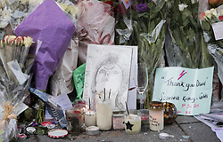 © Licensed to London News Pictures. 10/01/2017. London, UK. Tributes are placed at a mural and shrine to David Bowie in Brixton on the first anniversary of his death. David Bowie was born in Brixton, south London. Photo credit: Peter Macdiarmid/LNP